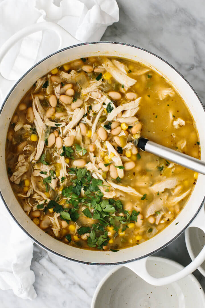 Cooking up white chicken chili in a large white pot