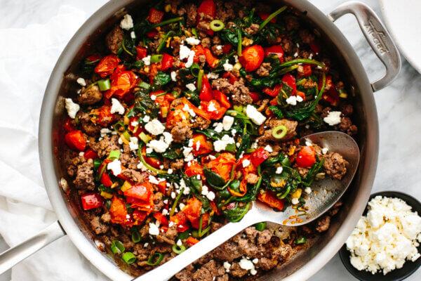 Mediterranean ground beef stir fry in a metal pan next to a napkin.