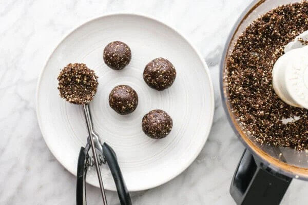 A cookie scoop with mint chocolate energy balls on a plate