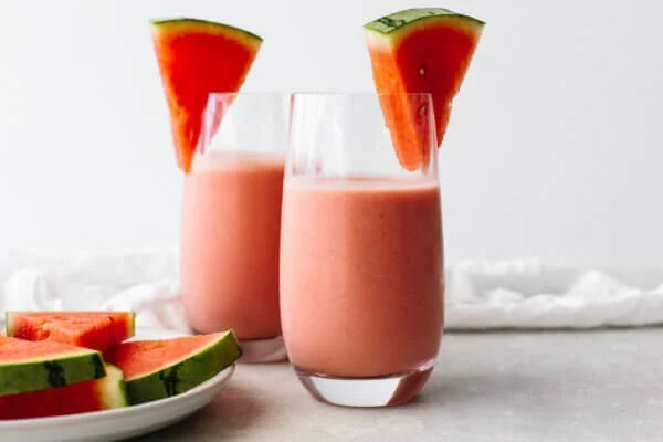Watermelon smoothie glasses on a table next to a napkin
