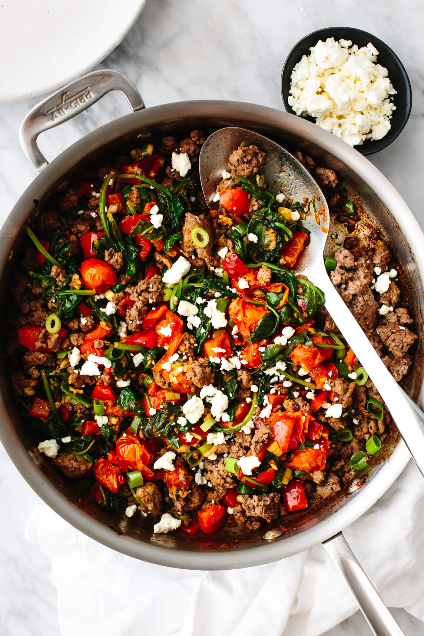 Mediterranean ground beef stir fry in a pan with a slotted spoon.