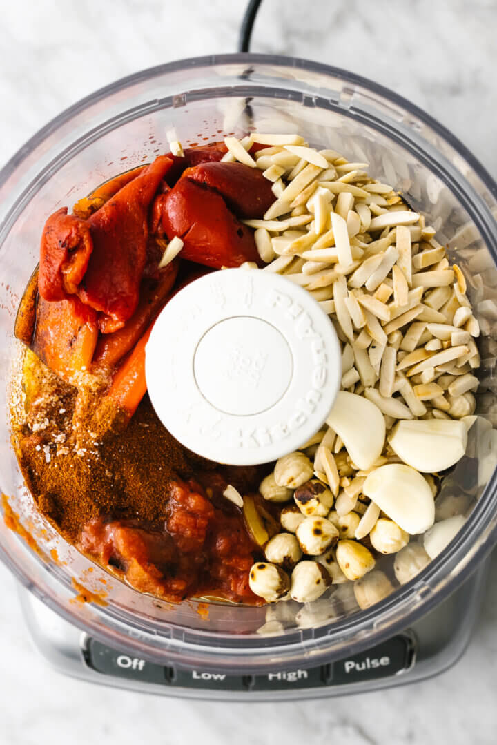 Adding all romesco sauce ingredients into a food processor
