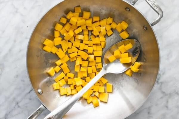 A wok with stir fry butternut squash