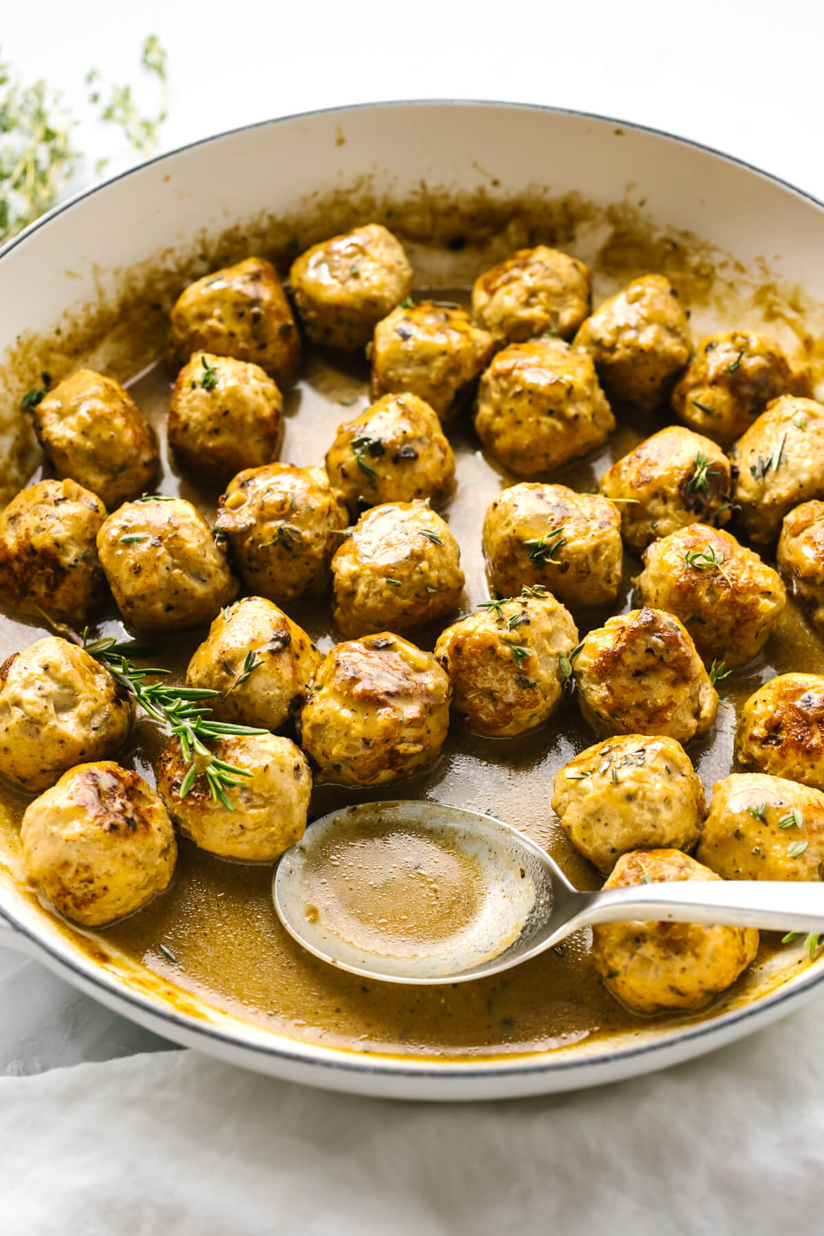 Turkey meatballs in a sauce in a pan with a spoon
