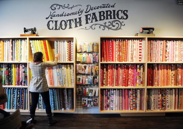 The Fancy Tiger Crafts has a new location at 59 Broadway. on Monday, January 16, 2012.  Manager Jessica Jeanne straightens fabrics along a wall at the craft store. Cyrus McCrimmon, The Denver Post