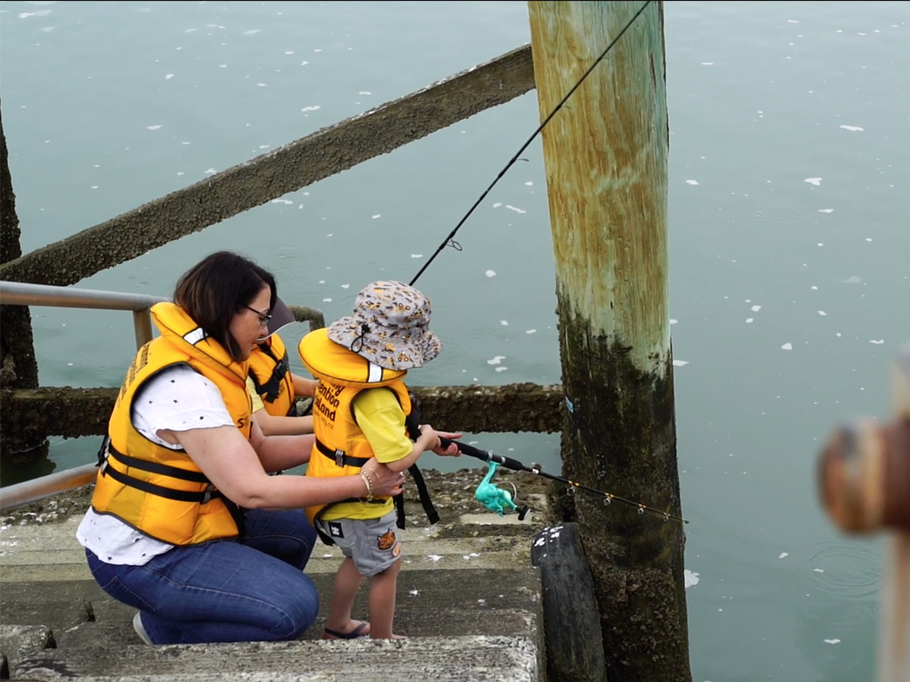 Young child fishing with Mum on jetty