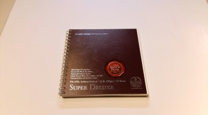 Bee Super Deluxe sketchbook showing cover printed with logos and advertising.