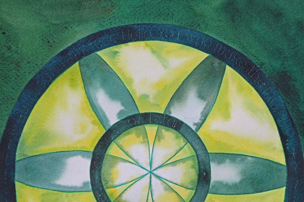 Green and yellow mandala with lettering.