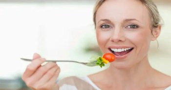 blog picture of lady eating tomato and other vegetables