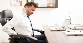 blog picture of man sitting in an office chair reaching for his lower back in pain