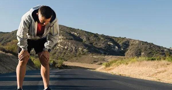 blog de imágenes del corredor de recuperar el aliento mientras se ejecuta en el camino alrededor de las colinas