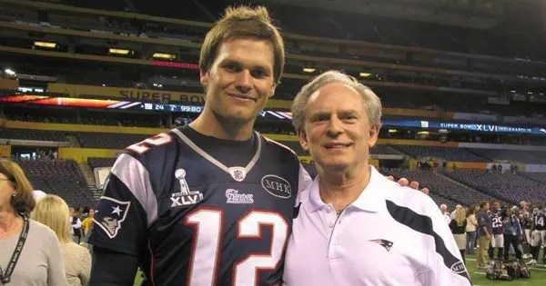 blog picture of football quarterback and chiropractor on field smiling for camera