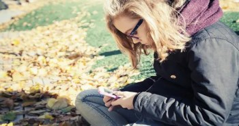 blog picture of a teenage girl sitting on grass and texting with her head down