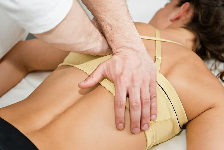 blog de imágenes de la señora acostada con las manos del Chiropractor que hace el ajuste en la espalda