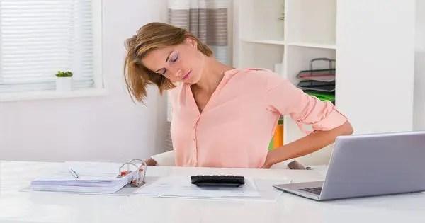 foto de blog de una dama en su escritorio con dolor de espalda