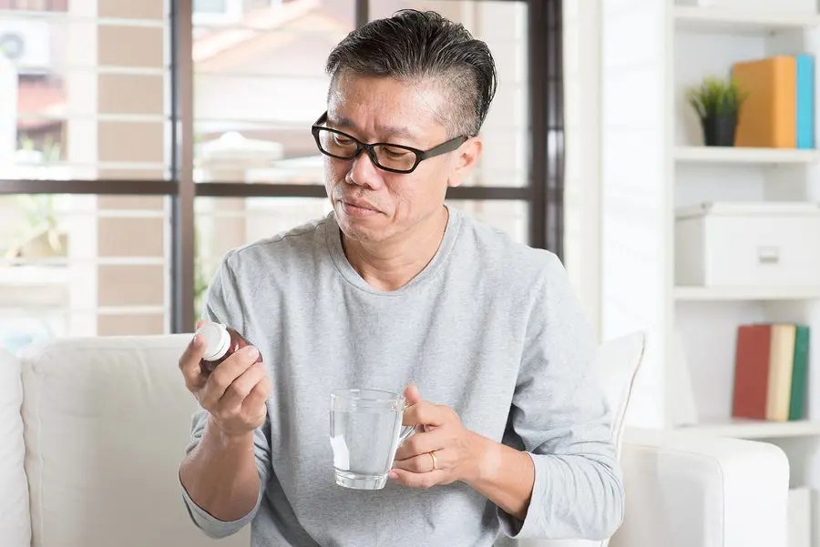 blog picture of man reading prescription pill bottle label