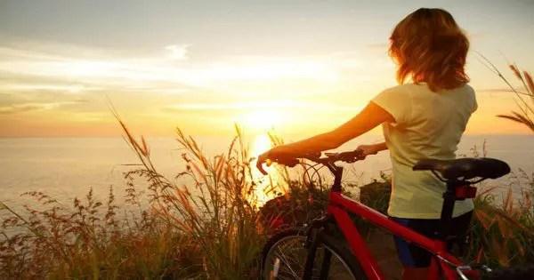 blog de imágenes de una señora que camina su bicicleta por el océano durante la puesta de sol