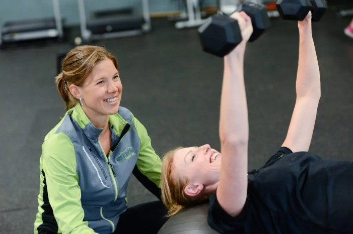 blog picture of woman working out with female trainer spotting