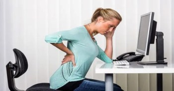 blog picture of lady at computer slumped over with lower back pain