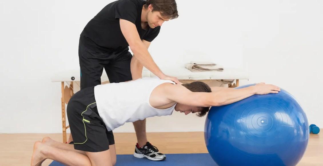 fisioterapeuta ayudando a hombre joven con pelota de yoga en el gimnasio en el hospital