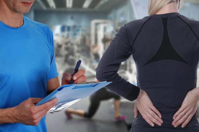 chiropractor takes notes on lady with back pain in gym