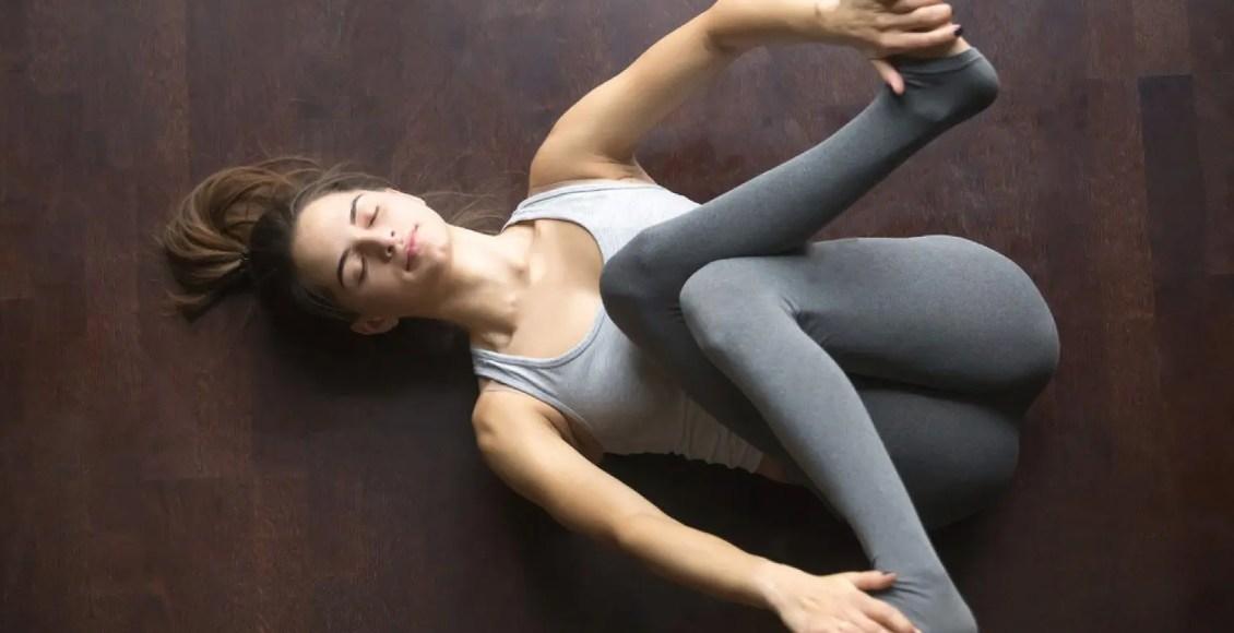 молодая модель, работающая на дому, занимаясь йогой на полу, лежащей в supta