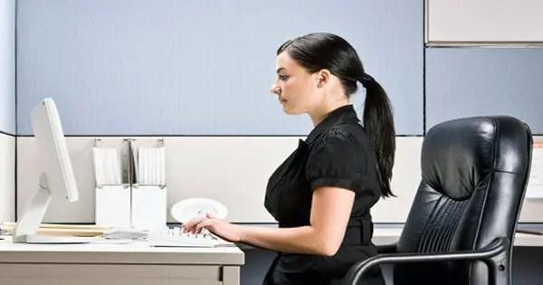 Señora sentada con la postura correcta en el escritorio de la oficina