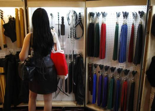Woman shops for whips, paddles and other kink gear.