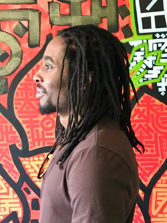 This is an after picture of a man with shoulder-length dreadlocks.