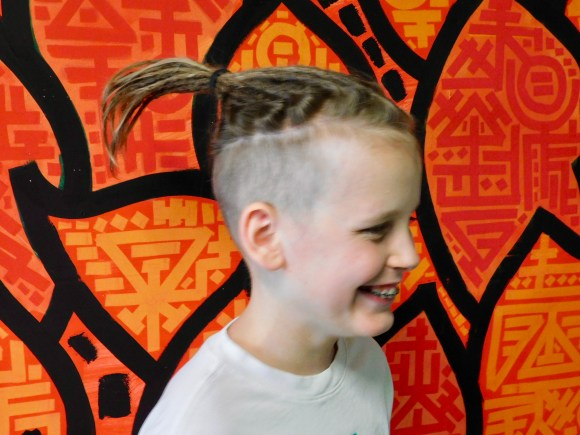 This picture shows a 12-year-old child with partial crochet dreadlocks on top of his head. He is smiling. The background is a red, orange and black mural.