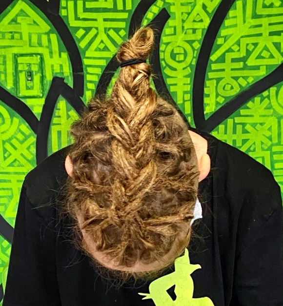 A dreadlock braid on the top part of my client's head. He's looking at the floor so you can see the entire braid.