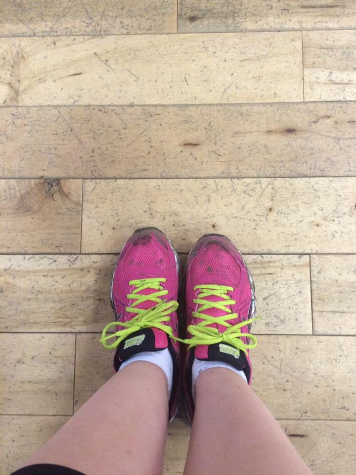 feet belonging to a Jolly Jogger, wearing a pair of pink trainers with yellow laces