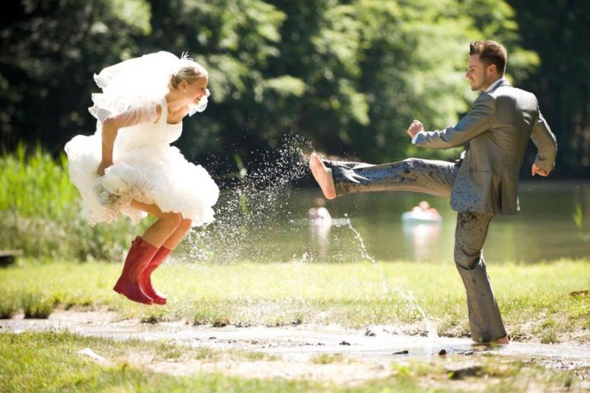 trash-the-dress-wedding-photo-bride-in-red-rain-boots-jumping-in-mud-puddle-with-groom