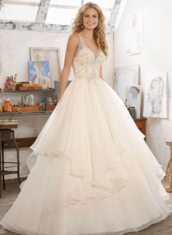 Madison Wedding Dress Romantic Bridal Ballgown Features Crystal Beaded Embroidery on Net with a Billowy, Flounced Organza Skirt. Open V-Illusion Back Accented with Covered Buttons. Shown in Champagne/Silver