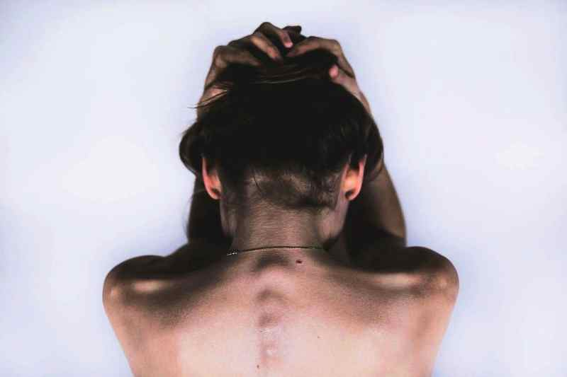 Woman with hands on head and spine bumps showing