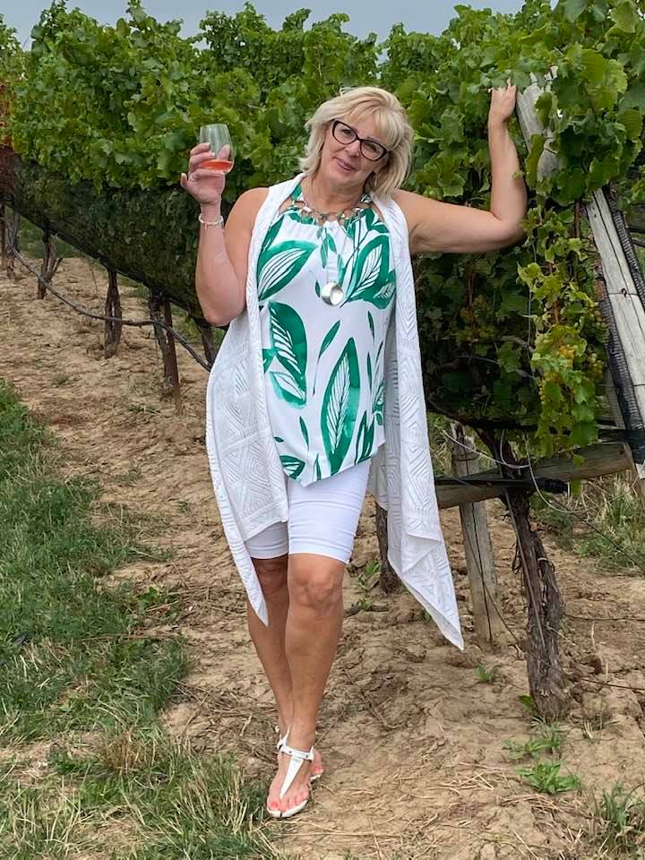 A photo of Lisa drinking wine in a Niagara Falls vineyard.