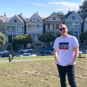 An image of Moshe standing outside the famous San Francisco Houses