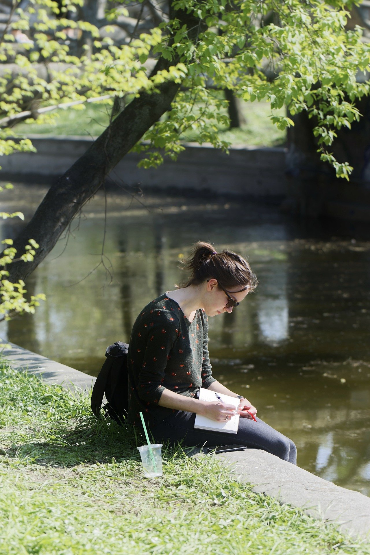Distance Learning can be done from anywhere, like in this photo of a girl next to a canal.