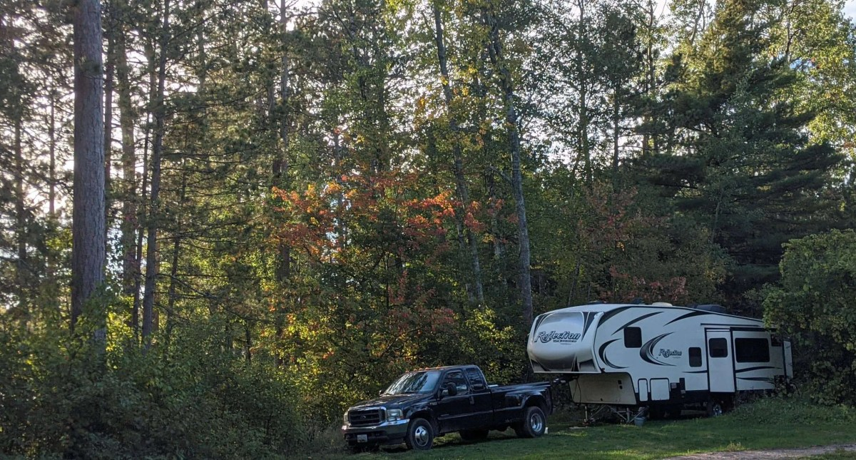 Dreams Built In - Full Time RV Family's Grand Design RV and Tow Truck parked in a National Forest in Minnesota