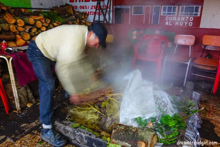 Opening the hole where the curanto is being cooked
