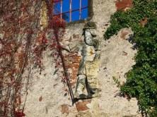 Skulptur in Mauer mit Rankpflanzen