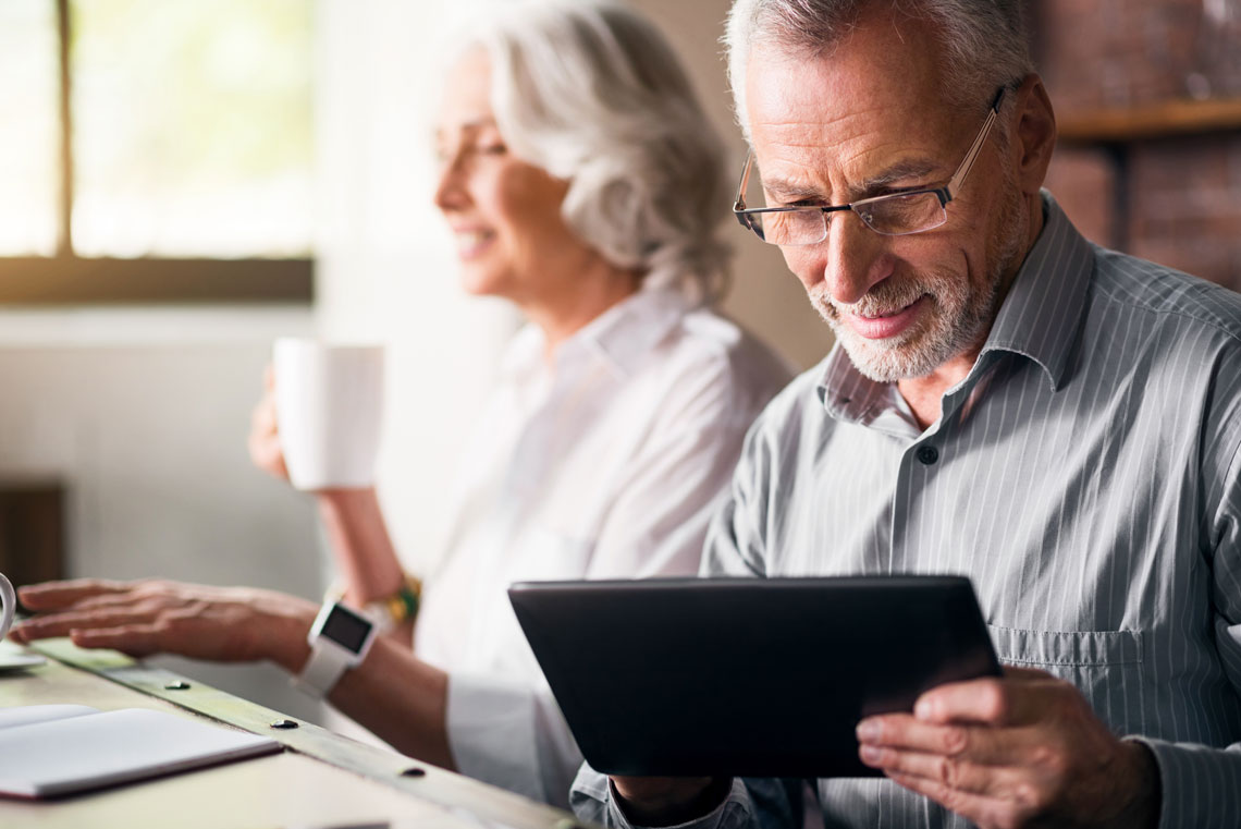an older adult couple reads the news about dr. hecker audiology via their tablet and laptop devices