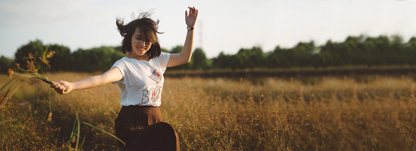 Young carefree woman frolicking in open field