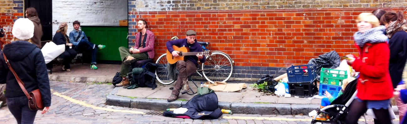 busker playing guitar at columbia road flower market london