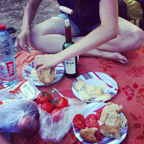eating bread, cheese and tomatoes in Provence, South France. With a bottle of red wine.