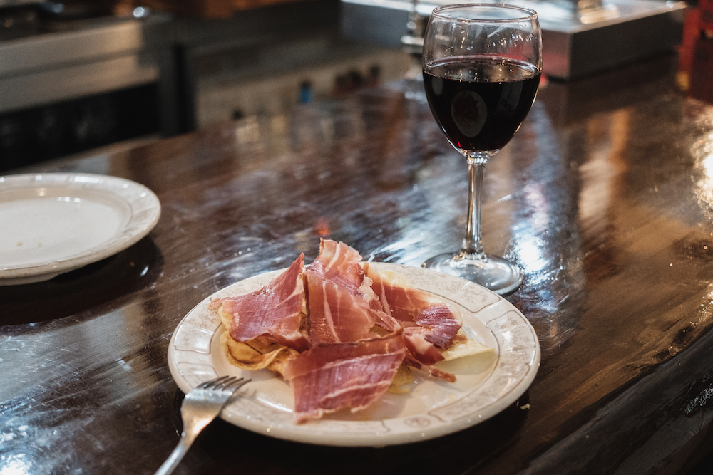 Eating free Spanish jamon tapas in a bar in Chueca Madrid