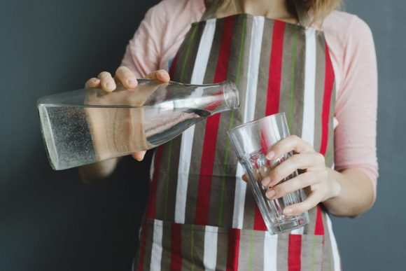 Woman pours clean drinking water into a glass.
