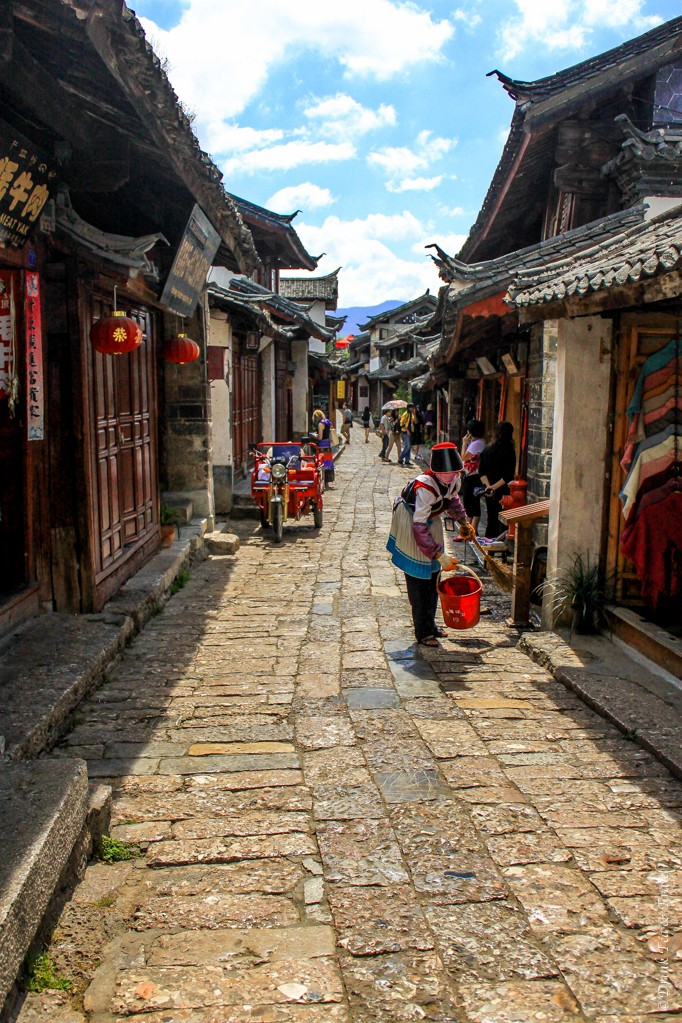 Woman cleaning in front of her shop in Lijiang, China