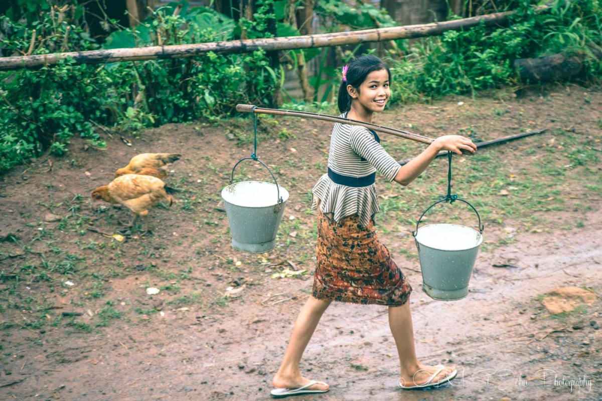 Young girl carries water to her home in Palaung Village