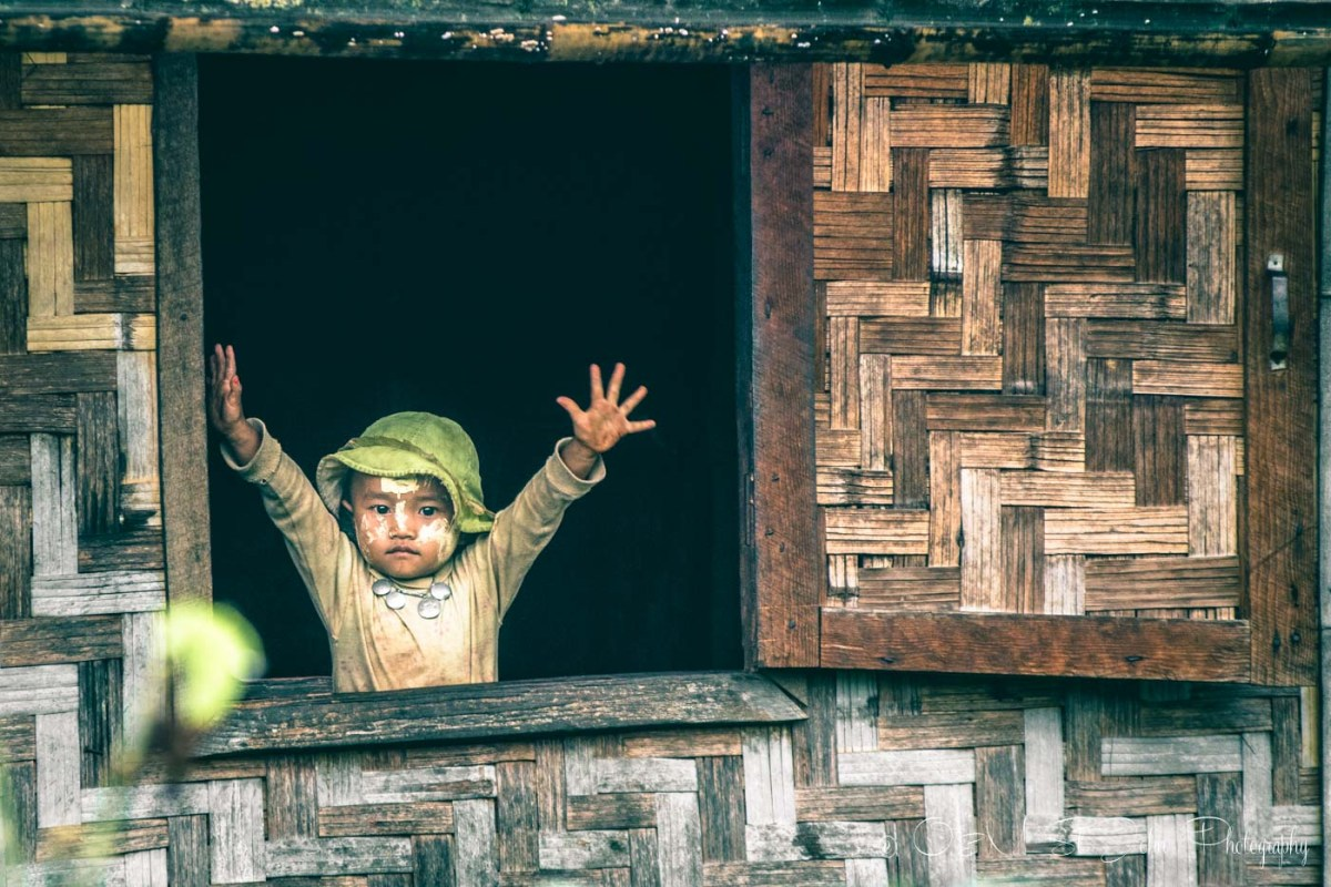Burmese boy greets passers by from the window of his house in a hill tribe village in Myanmar